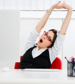Young businesswoman sitting at desk yawning at Twitter