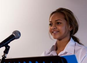 Female student making a speech. She is standing at a podium and smiling to the crowd.